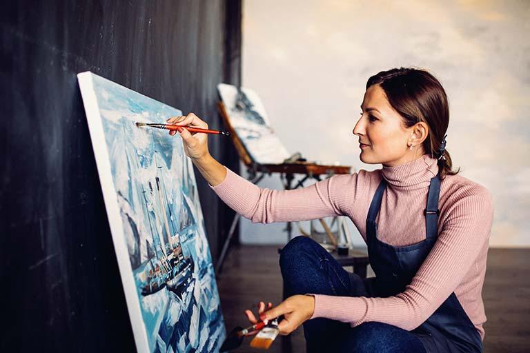 אמנית בתהליך היצירה של ציור